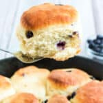 blueberry biscuit on spatula above iron skillet